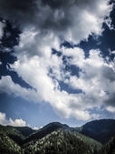 Blue sky with clouds under the mountains. — Stock Photo