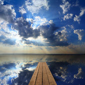 Wooden pier on big lake and sky reflection — Photo