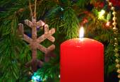 Christmas - candle and wooden snowflake on fir — Stock Photo