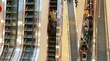 People in motion on escalators at the modern shopping mall — Stock Video