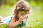 Kid with magnifying glass — Stock Photo