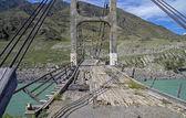 View through the old bridge over mountain river. — Stock Photo