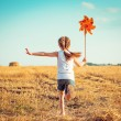 Cute little girl with a  windmill — Stock Photo #54525621