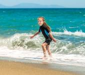 Girl in a wetsuit on the beach — Stock Photo