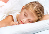 Little girl sleeping in white bed — Stock Photo