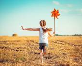 Cute little girl with a  windmill — Stock Photo