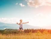 Klein meisje loopt door een weide — Stockfoto