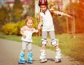 Two little sisters in a roller skates — Stock Photo