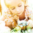 Girl with magnifying glass looks at flower — Stock Photo #54536711
