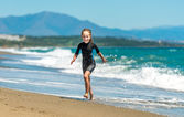 Girl in a wetsuit on beach — Stock Photo