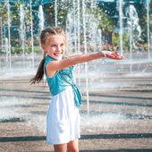 Little girl having fun in fountain — Stock Photo