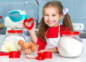 Little girl holding a cookie cutter — Stock Photo