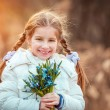 Little girl with a snowdrops — Stock Photo #64329943