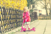 Year-old girl riding her scooter — Photo