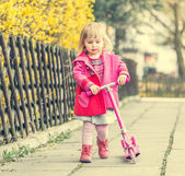 Jarige meisje haar scooter rijden — Stockfoto