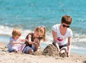 Mother and daughters playing in  sand — Stock Photo