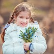 Little girl with a snowdrops — Stock Photo #71968867