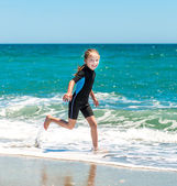 Girl in  wetsuit on beach — Stock Photo