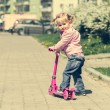 Little  girl riding her scooter — Stock Photo #74335111