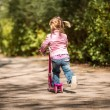 Little  girl riding her scooter — Stock Photo #74335221