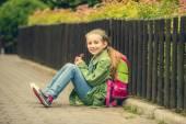 Красивая школьница, сидя на улице — Стоковое фото