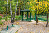 Bench and pavilion in autumn park — Stock Photo