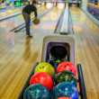 Bowling balls and player on blurred background — Stock Photo #58020637