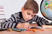 Cute schoolboy writting — Stock Photo