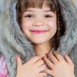 Cute little happy girl posing in a fur hat. — Stock Photo #59281221