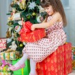 Happy little girl with christmas present smiling — Stock Photo #59281339