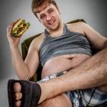 Fat man eating hamburger — Stock Photo #65048827