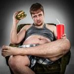 Fat man eating hamburger — Stock Photo #65048841