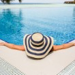 Woman in straw hat relaxing swimming pool — Stock Photo #70112803