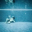 Persons lies under water in a swimming pool — Stock Photo #84809588