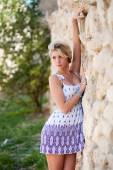 Beautiful sensual girl standing near stone wall — Stockfoto