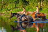 Two young men astride horses — Stock Photo