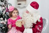 Little girl with a gift  and Santa Claus — Stock Photo