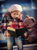 Girl reads the book to a toy bear — ストック写真