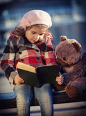 Girl reads the book to a toy bear — 图库照片