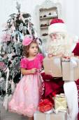 Girl with a gift in hands and Santa Claus — Stock Photo