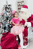 Little girl sits on a lap at Saint Nicolas — Stock Photo