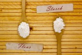 Wooden spoon with flour and starch — Stock Photo