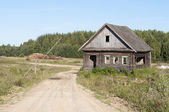 Dirt road and abandoned wooden house — Stock Photo