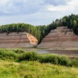 Постер, плакат: Geological outcrop on the riverbank with deep ravine