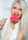 Young sexy blonde woman with heart shaped lollipop — Stock Photo