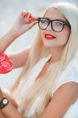 Young sexy blonde woman with heart shaped lollipop and sunglasses. Outdoor. — Stock Photo
