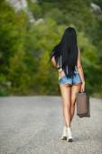 Lonely Girl with a suitcase on a country road ... — Stock Photo