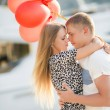Young couple with colourful balloons in town. — Stock Photo #52286153