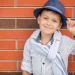 Stylish boy in Hat posing on a brick wall — Stock Photo #52286507