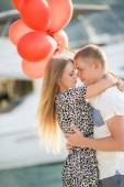 Young couple with colourful balloons in town. — Stock Photo
